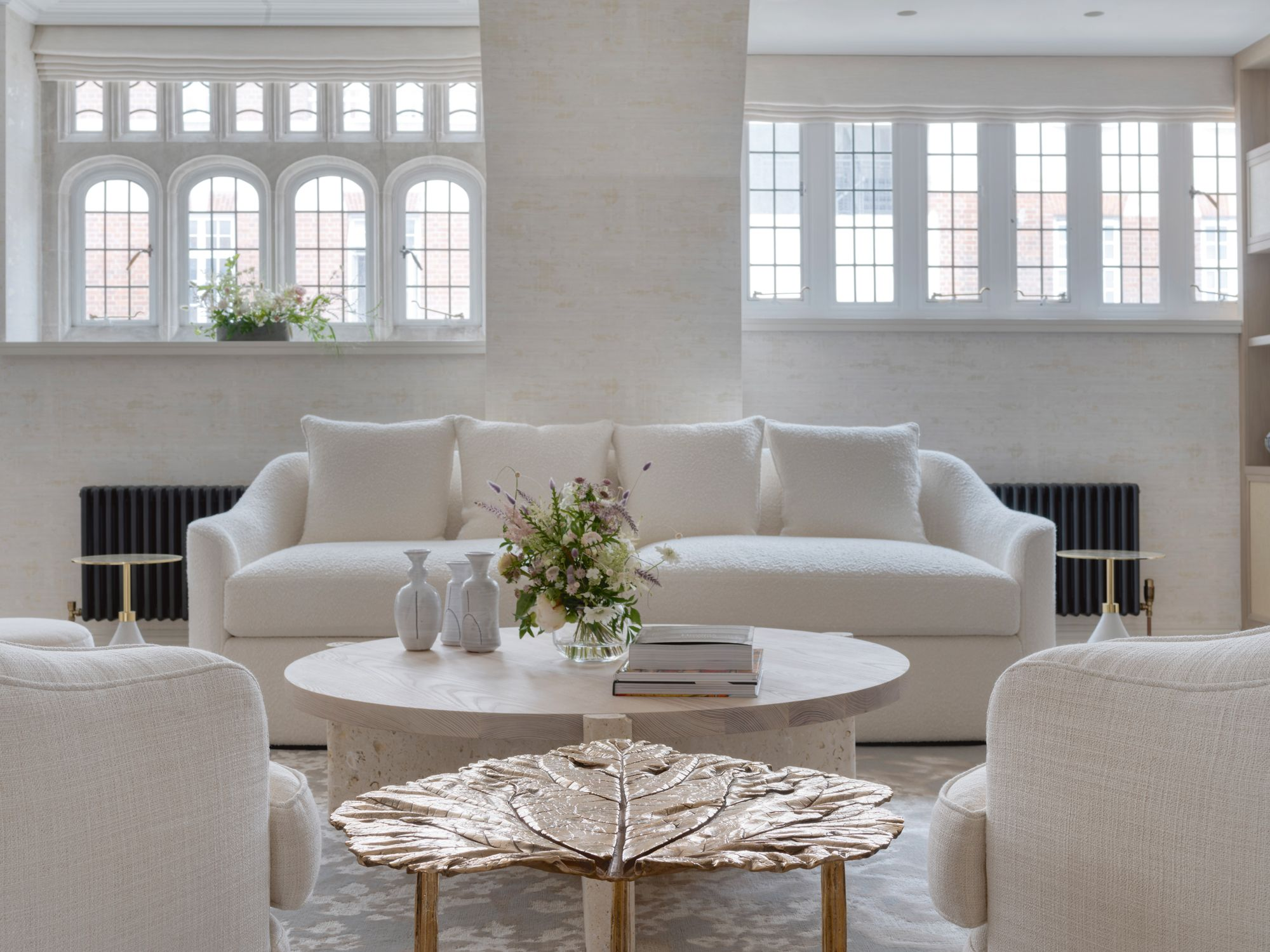 A gold-leaf side table by Clotilde Ancarani adds a glamorous touch to the monochromatic living room
