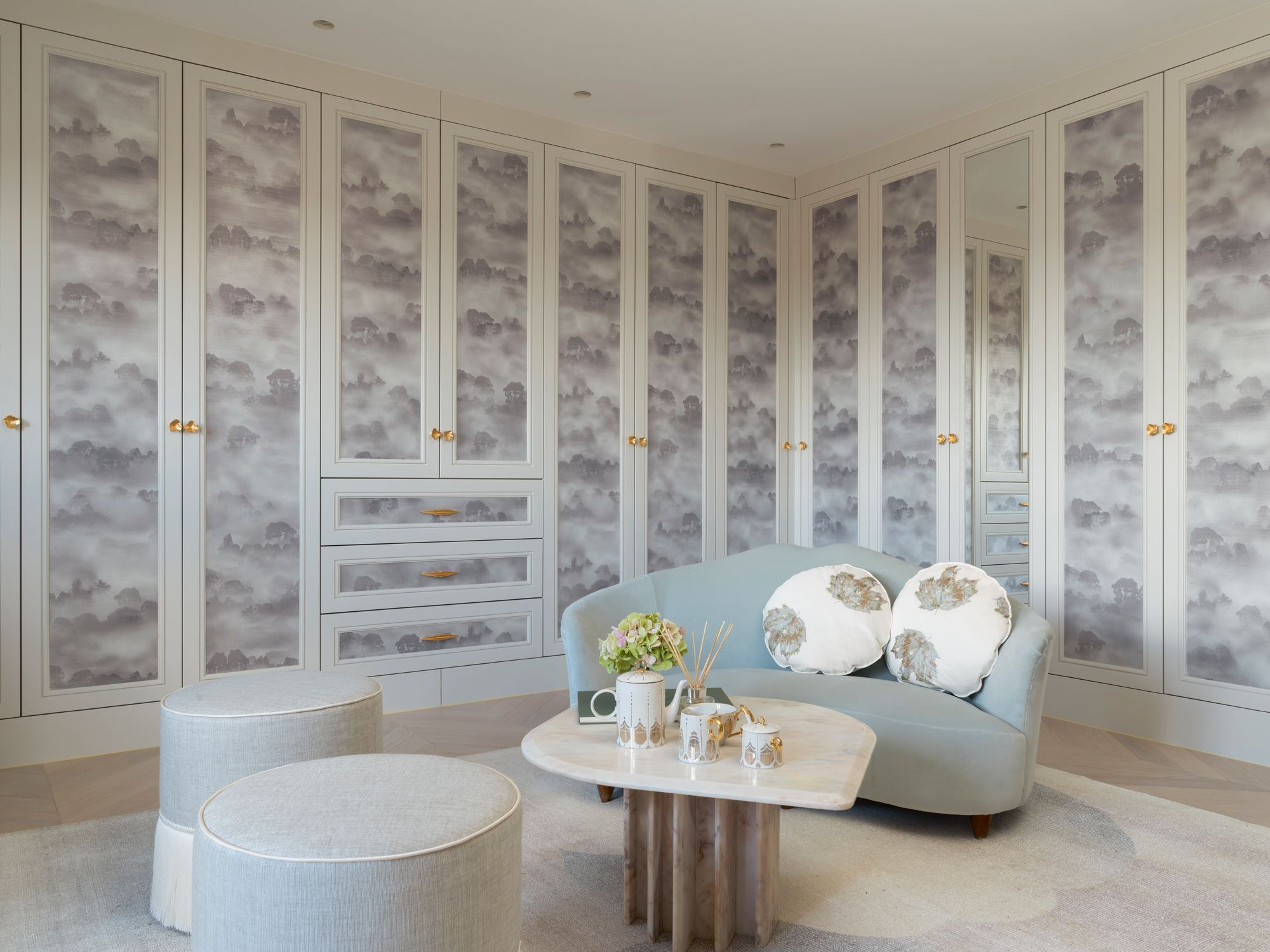 The master wardrobe features custom cabinetry with a dreamy pattern inspired by cloudy skies