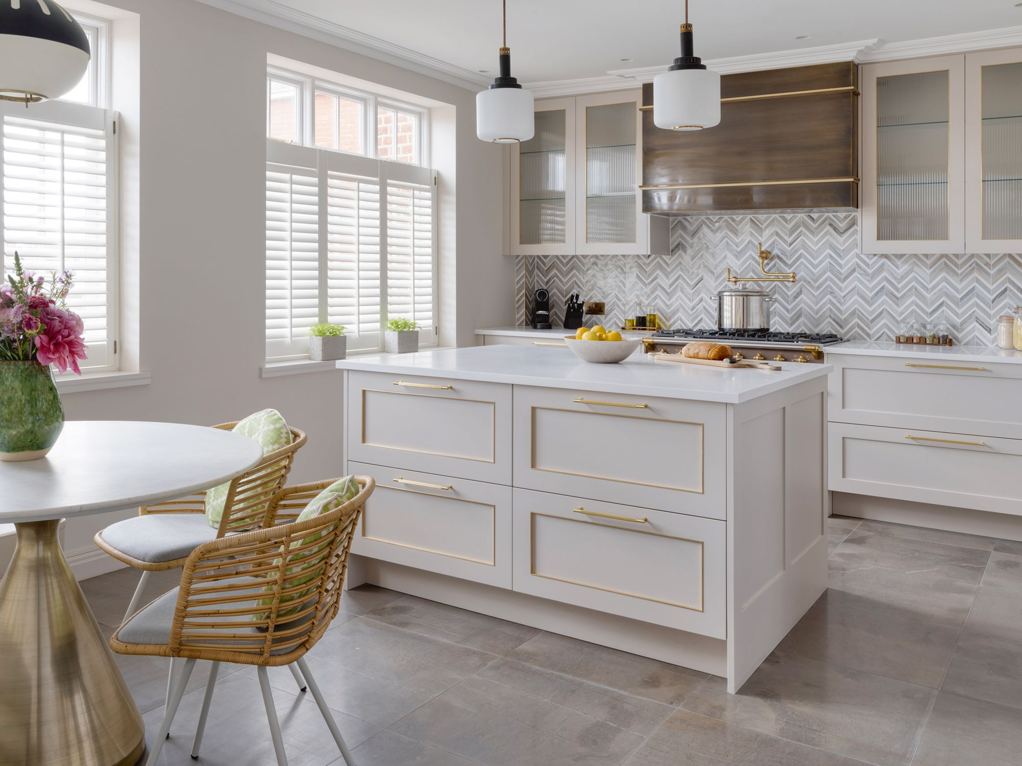 A herrigbone-patterned backsplash and Grigio Tunisi marble flooring contribute to the layered look of the kitchen's neutral scheme