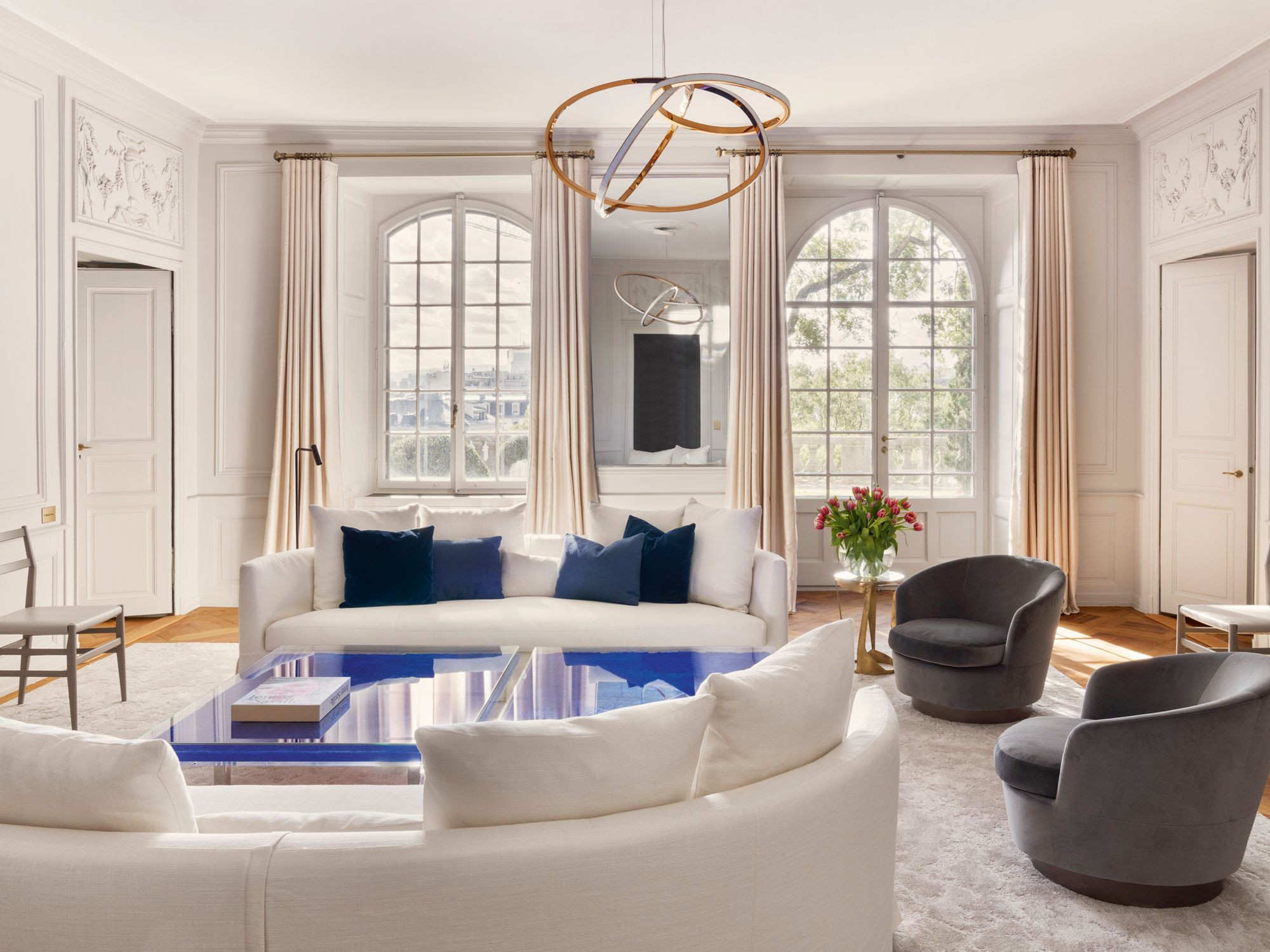 The living room is adorned with a pair of B&B Italia Maxalto Crono sofas, Cassina 646 Leggera chairs by Gio Ponti, Minotti Jacques armchairs, Vincenzo de Cotiis DC1511 side table and the Sum of One and Two hanging lamp by Niamh Barry