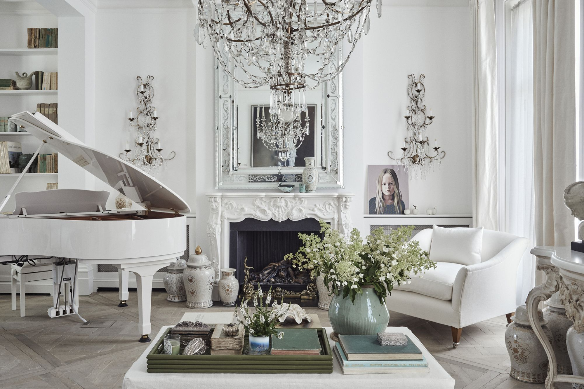 A Venetian Murano glass mirror by Signorelli sits grandly above a bespoke marble fireplace carved with striking Statuario marble