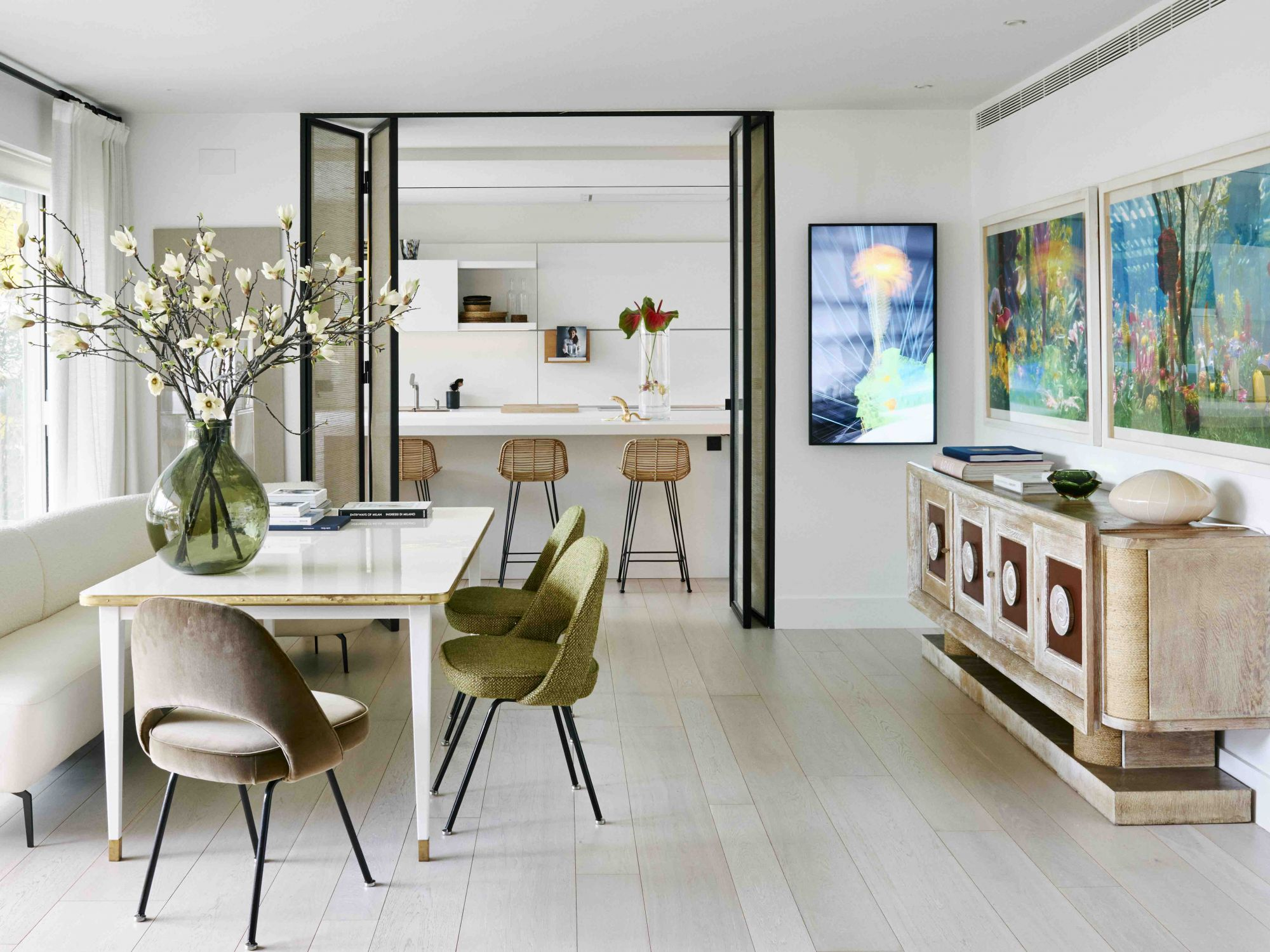 La salle à manger comprend les chaises Knoll Executive d'Eero Saarinen, une paire d'œuvres d'art de Marc Quinn et l'art numérique de Miguel Chevalier de Ventana Contemporary