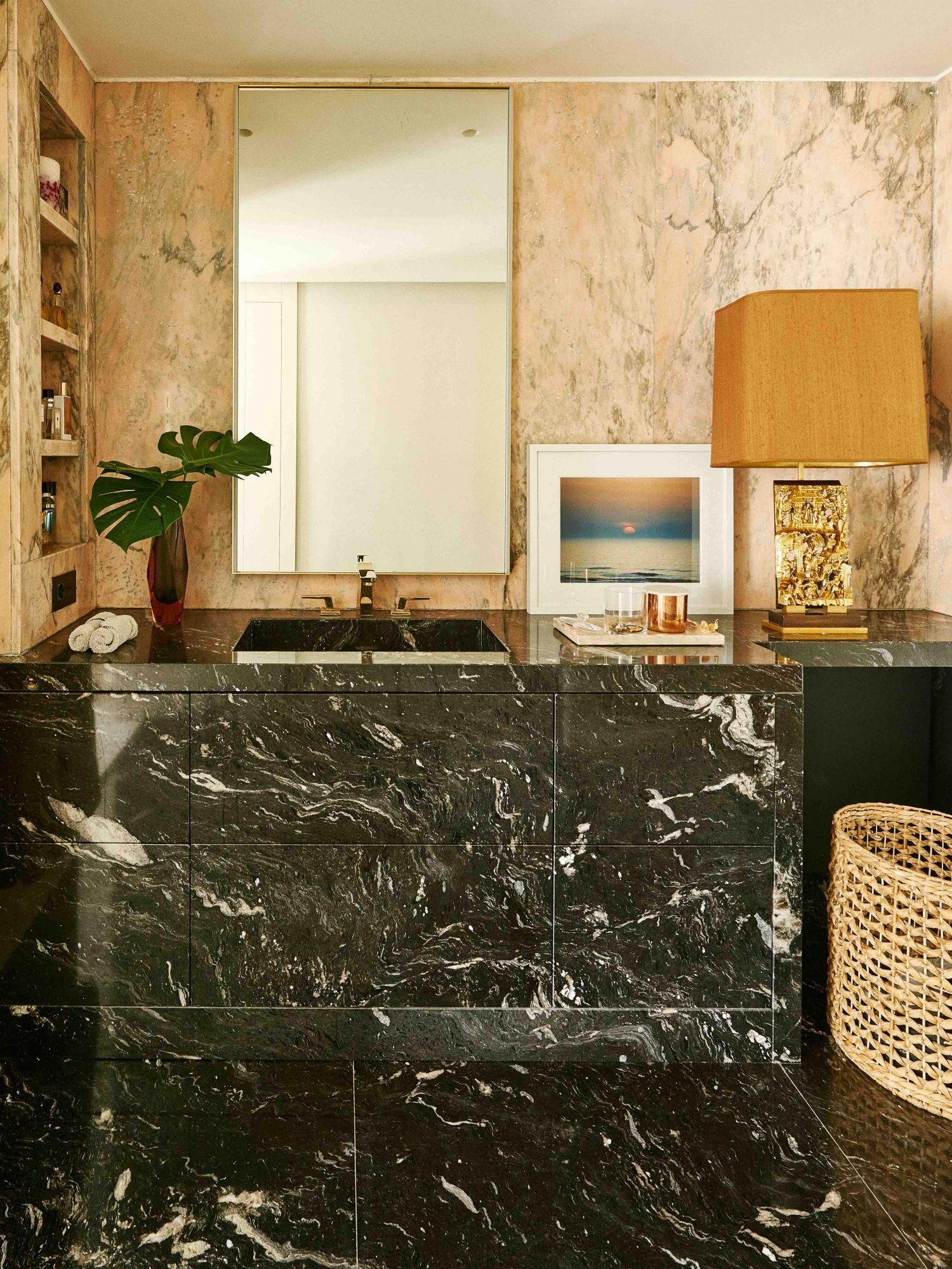 La salle de bain principale est un espace glamour avec du granit noir Cheyenne, des murs en marbre rose portugais et des robinets en or de Dornbracht