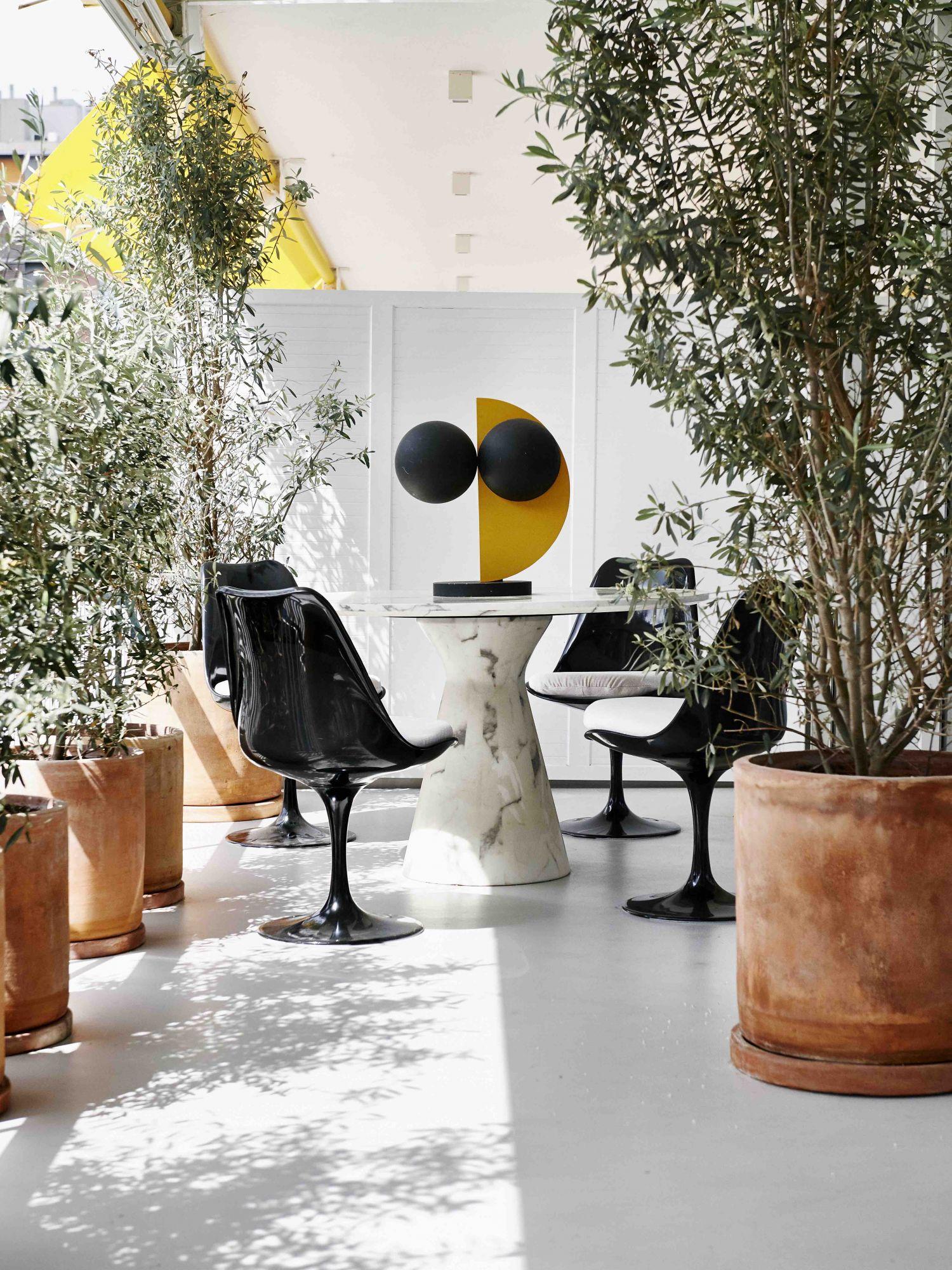 La salle à manger extérieure est meublée avec des chaises Knoll Tulip d'Eero Saarinen, une table de Recdi8 Living et une sculpture en bois de Rob Van Dam