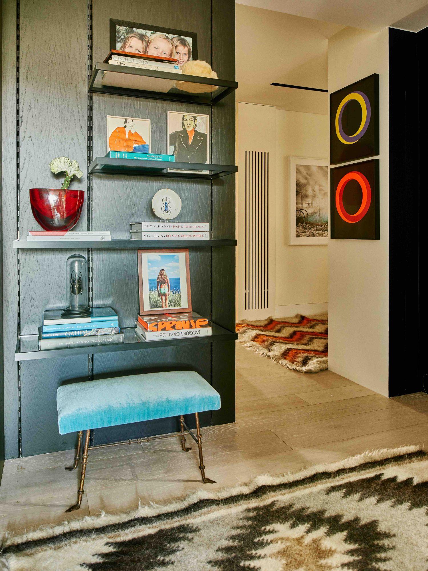 Un banc vintage de 177 Kensington et un souvenir coloré ajoutent des touches de couleur au mur en bois sombre