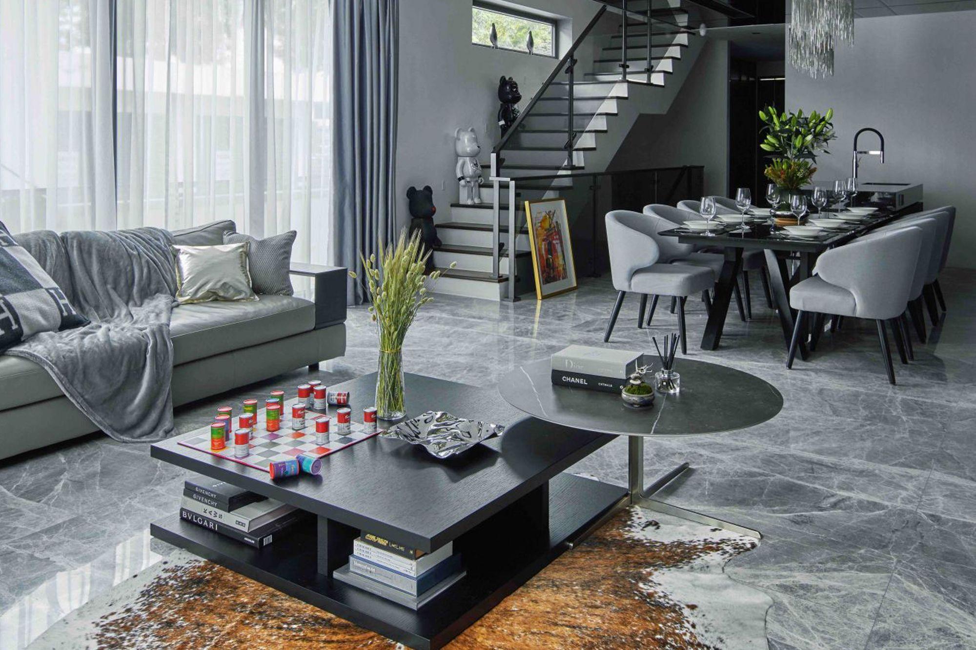 Die grauen Akzente der gemütlichen Decke und Kissen auf dem Sofa im Wohnzimmer spiegeln sich in den weichen Esszimmerstühlen wider, die den Raum verbinden Fotografie: Jasper Yu