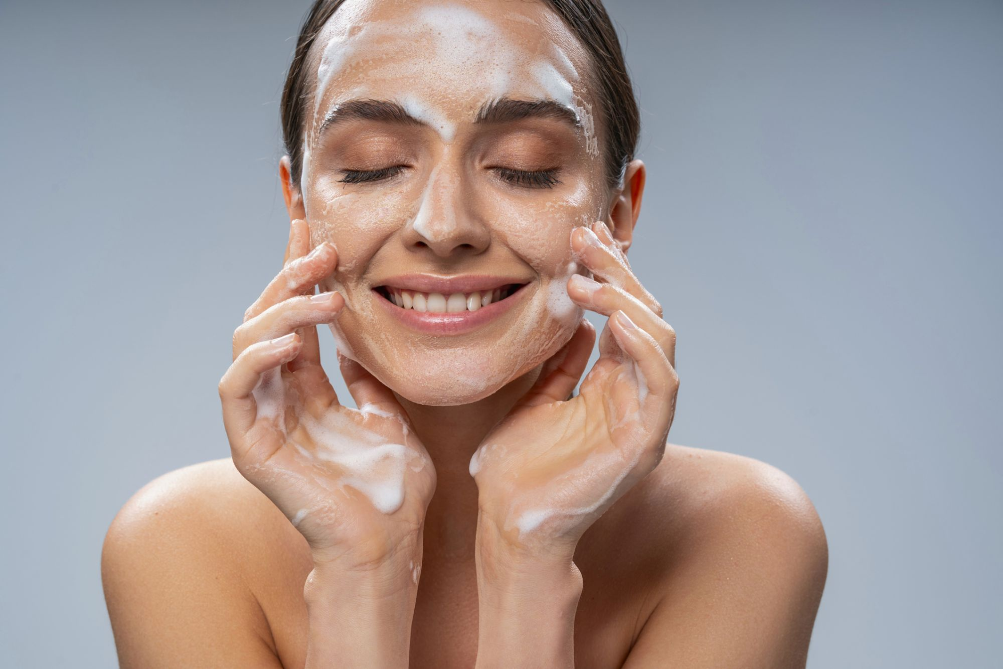 Portrait of smiling attractive woman touching face by hands while cleansing the skin from makeup. Isolated on grey background. Cosmetics and care concept