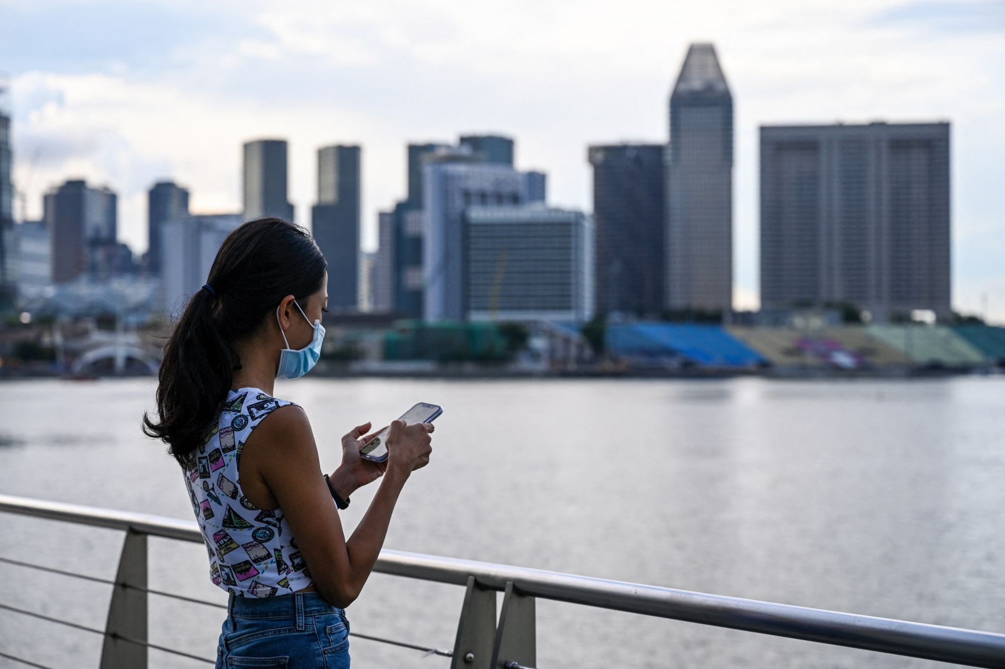 This picture taken on May 7, 2021 shows an advertising executive who wanted to be known as Erica checking her mobile phone along the Marina Bay promenade in Singapore. - Erica is among a growing number of women travelling overseas to get their eggs frozen, as people in the work-obsessed city-state increasingly delay having children. (Photo by Roslan RAHMAN / AFP) / TO GO WITH Singapore-Malaysia-women-fertility, FEATURE by Catherine Lai and Sam Reeves