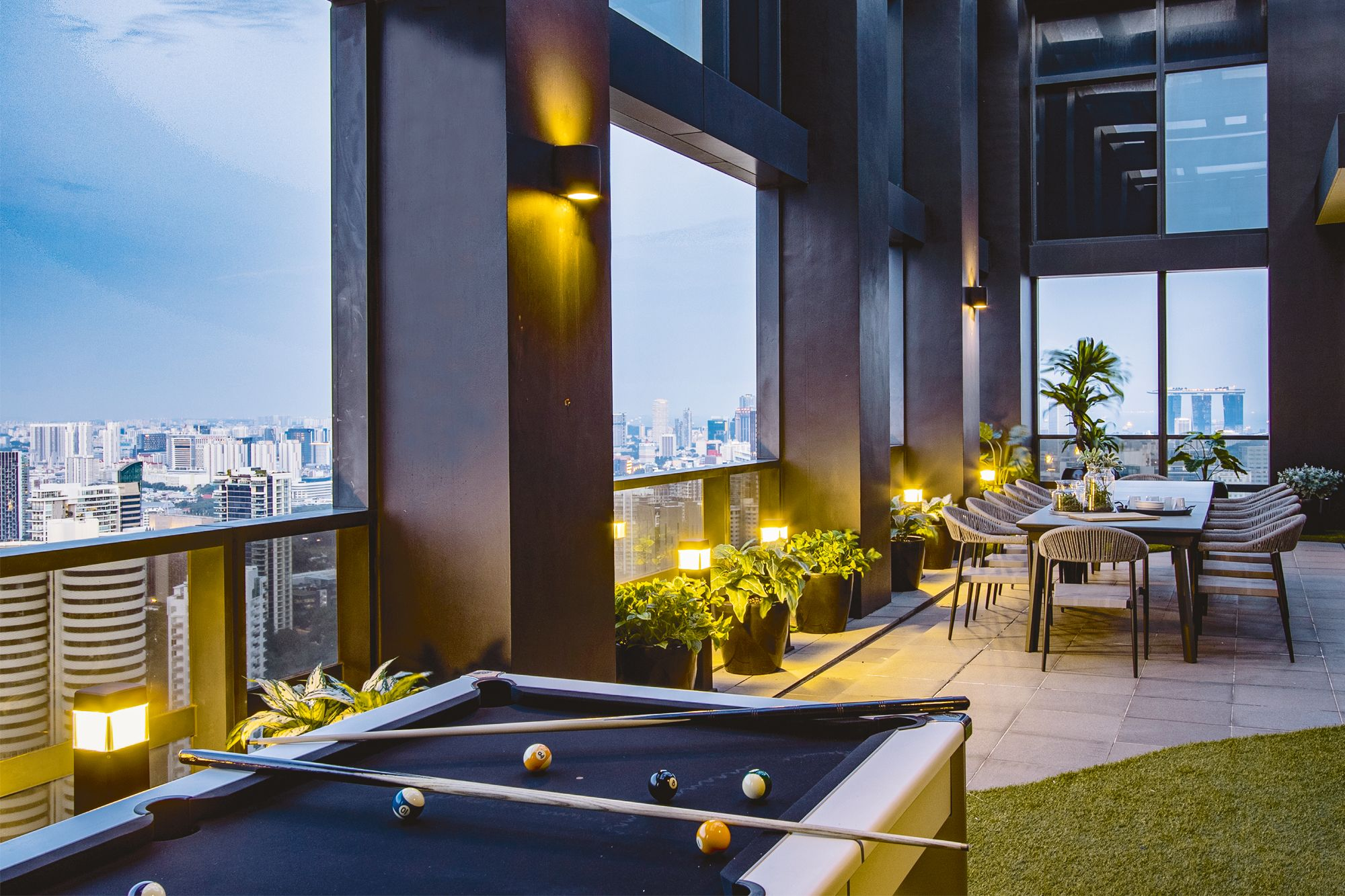 The spacious rooftop area features a twelve-seater outdoor dining set and a pool table