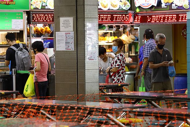 People wearing protective masks queue to buy a takeway food at a hawker centre. Photo: Suhaimi Abdullah/Getty Images