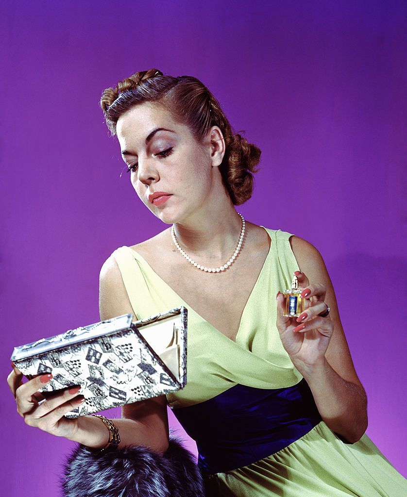 A woman holding a perfume bottle while looking into her clutch purse, New York City, 1943. (Photo by Constance Bannister Corp/Getty Images)