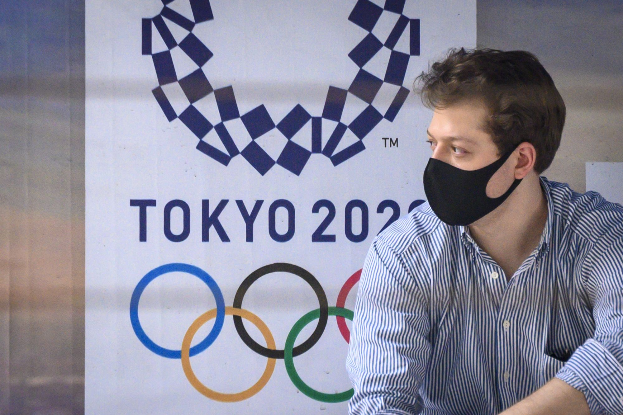 A man wearing a facemask, amid concerns over the spread of the COVID-19 coronavirus, sits at a bus stop in front of a Tokyo 2020 Olympics advertisement in Bangkok on March 16, 2020. (Photo by Mladen ANTONOV / AFP)