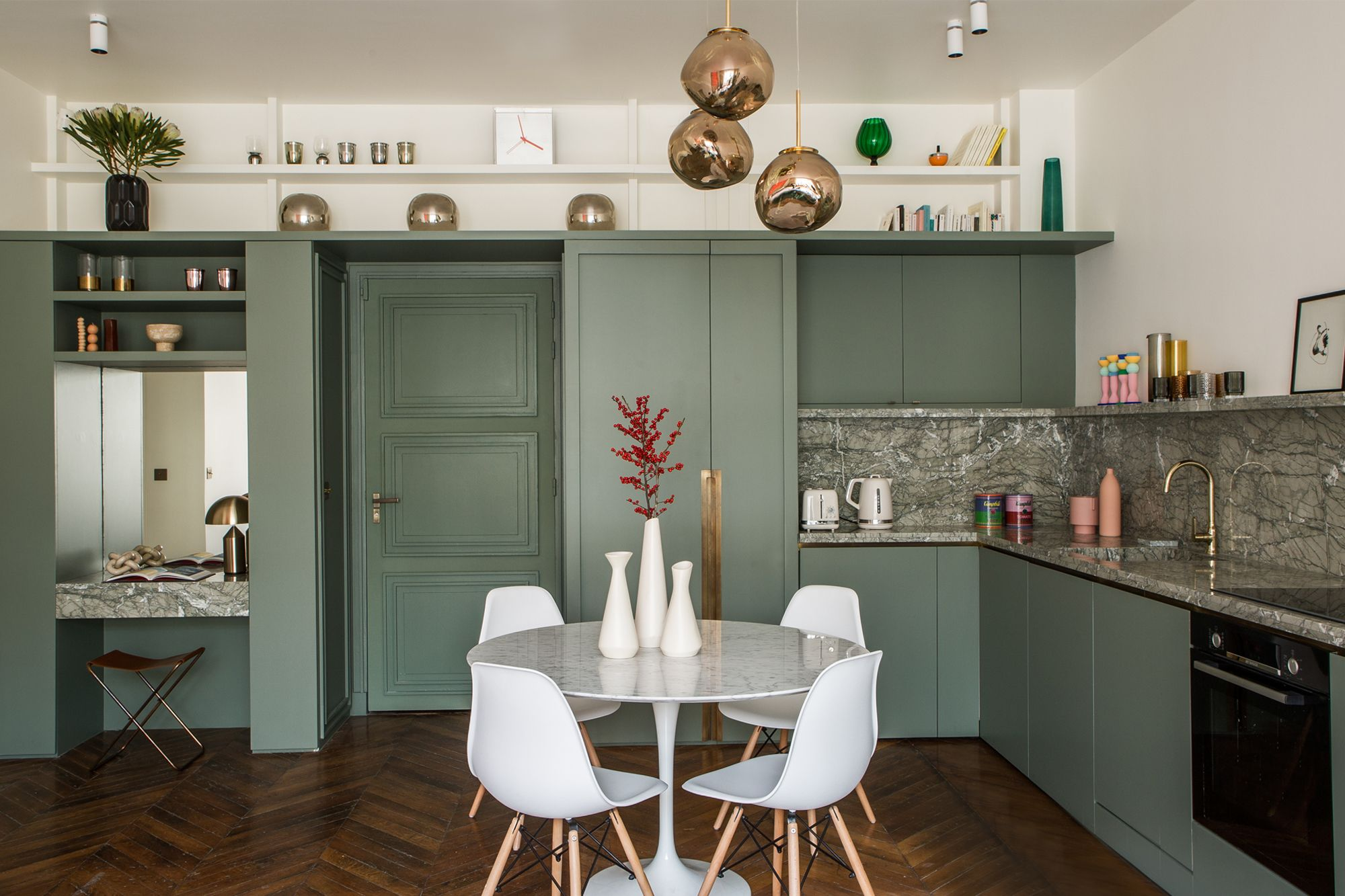 The kitchen is painted in a single green hue to create a contemporary space that pops