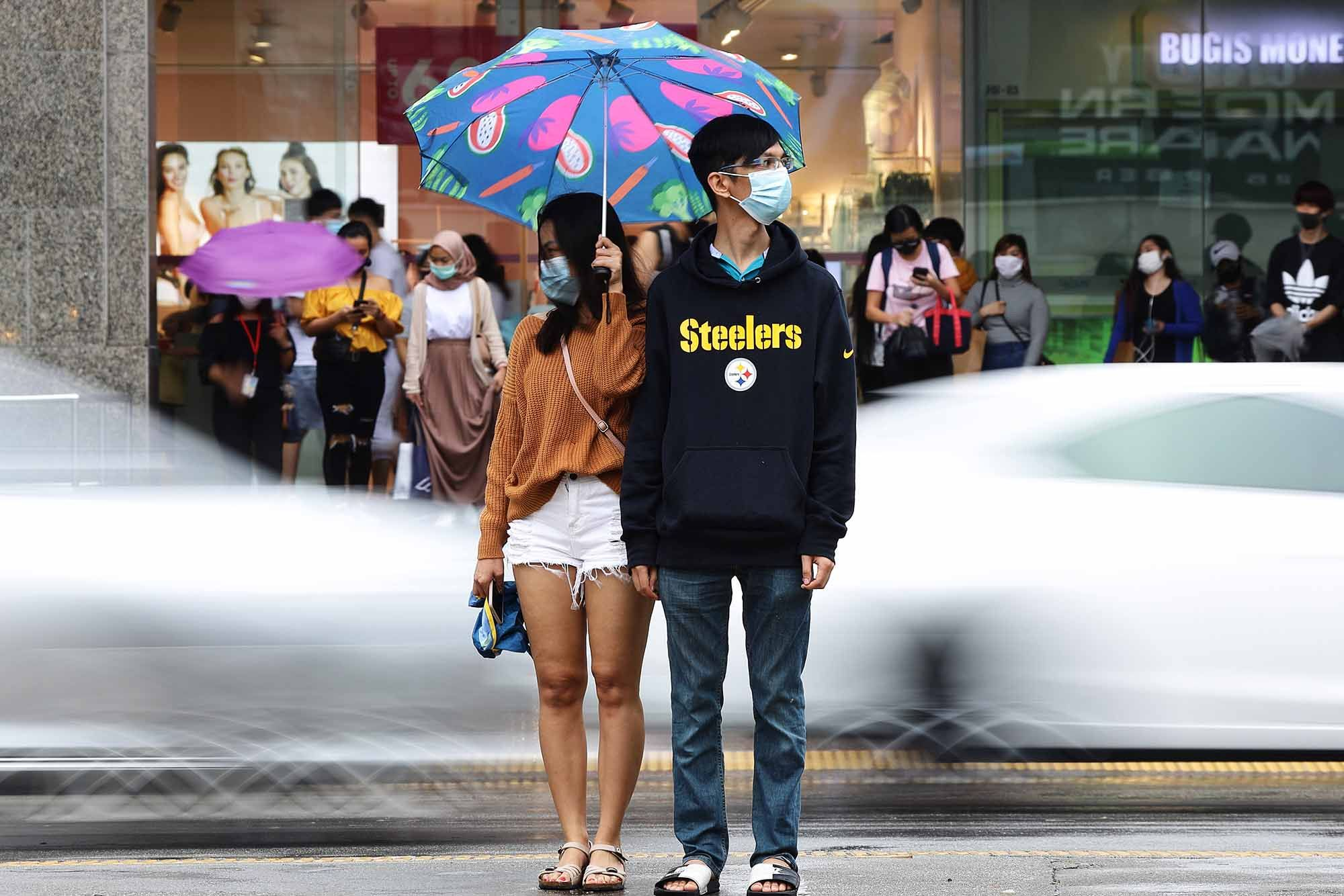 A couple wearing protective masks wait to cross a street in the rain. (Photo: Getty Images)
