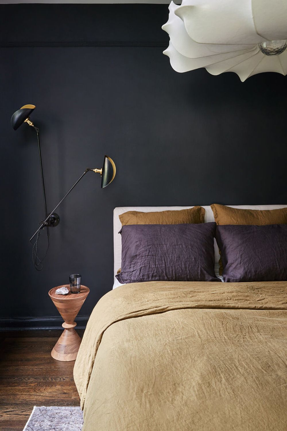 Designed by Tali Roth Interior Design, this black bedroom features light textiles and decorative lighting to inject brightness into the space Photography: Seth Caplan, courtesy of Tali Roth Interior Design