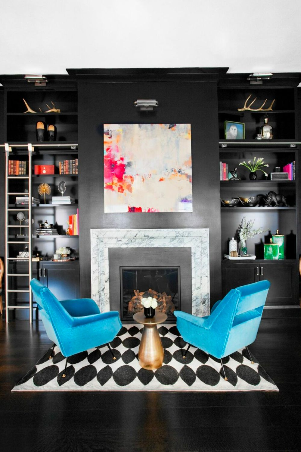 This contemporary fireplace designed by Nicole Fuller features dark bookcases paired with eclectic artworks for a vibrant touch Image: Courtesy of Nicole Fuller Interiors