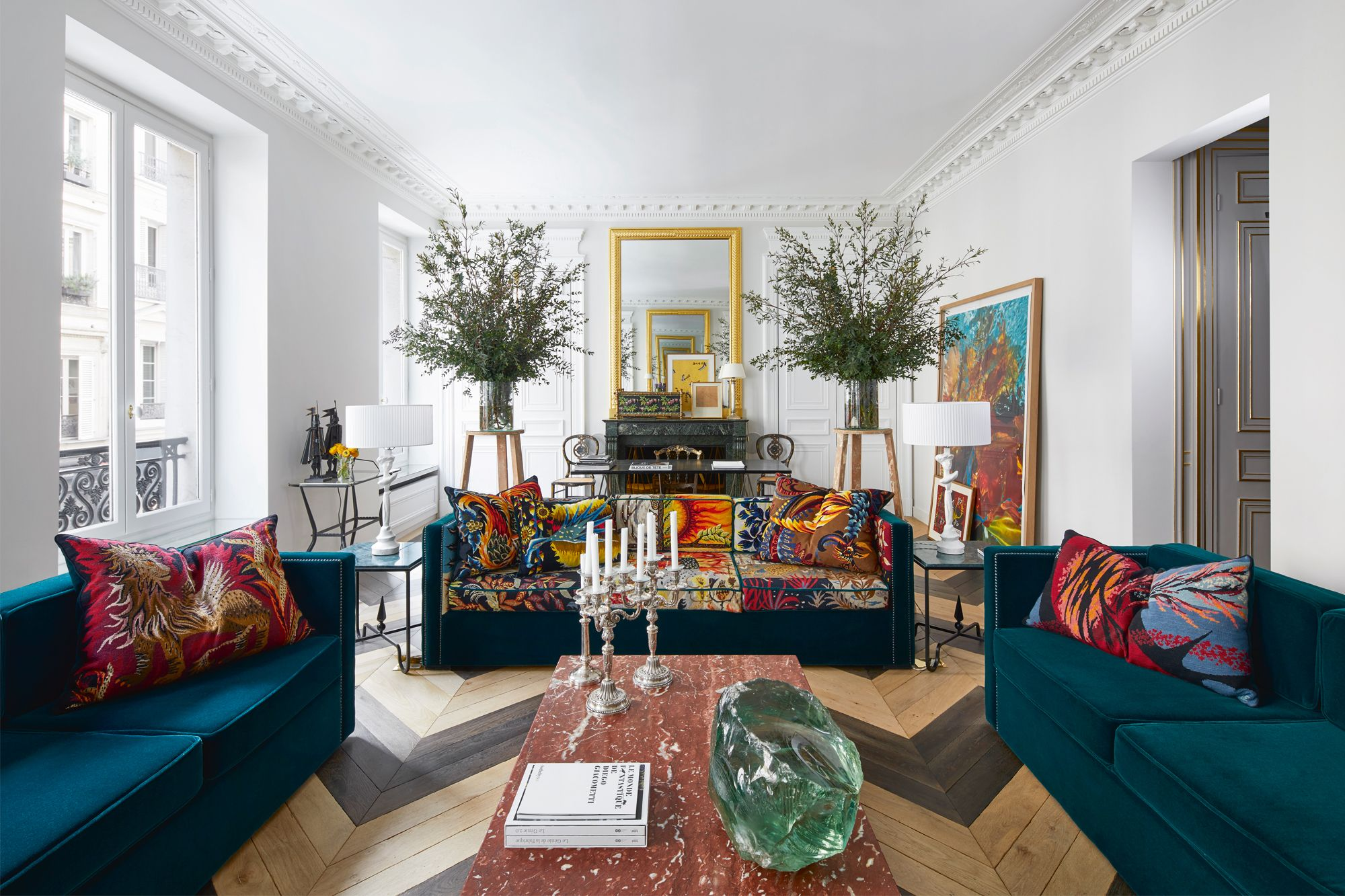 A large painting by Gilles Bensimon echoes the hues on the colourful custom velvet sofas and accent cushions