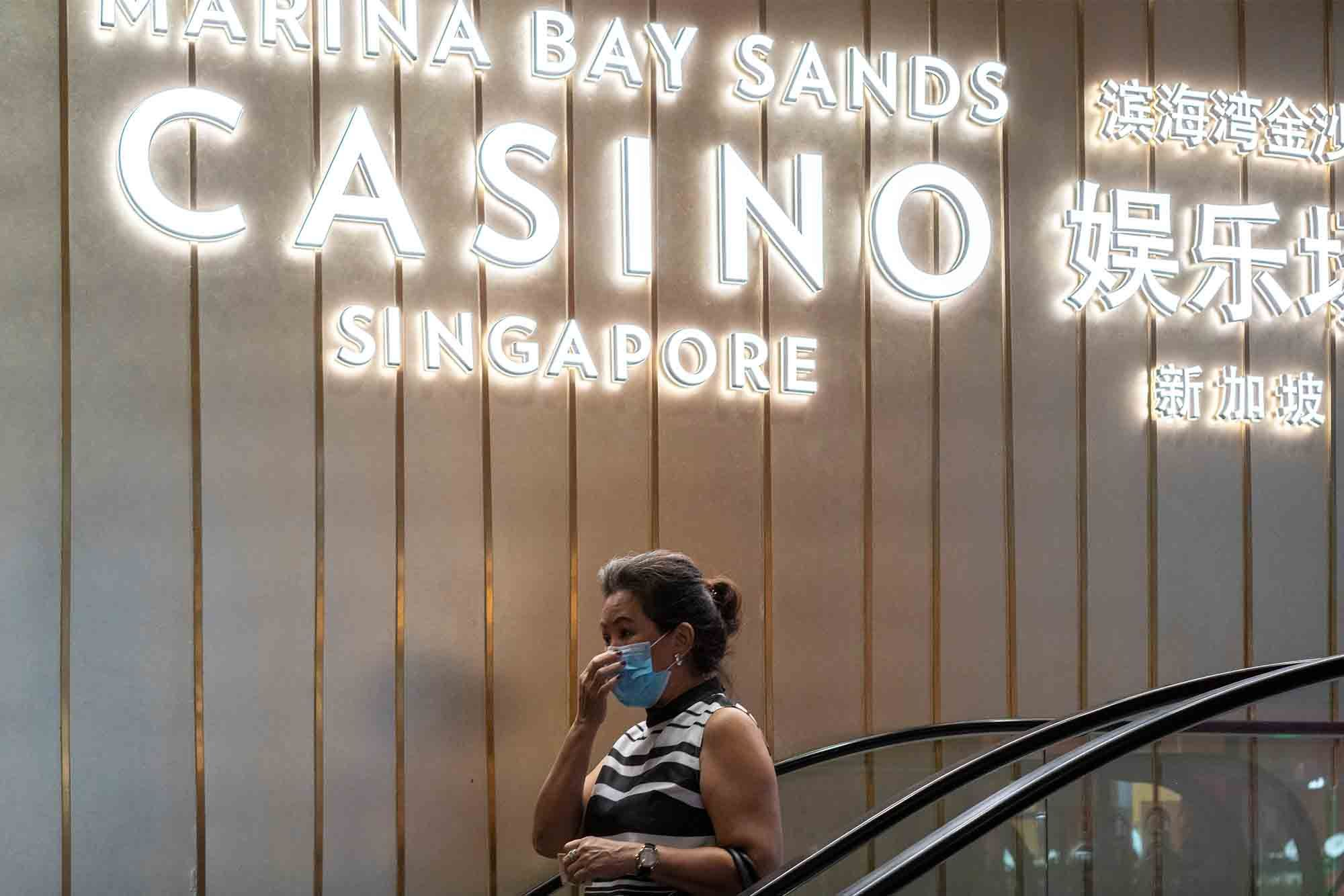 A woman wearing a protective face mask walks past a Marina Bay Sands Casino signage. (Photo: Getty Images)
