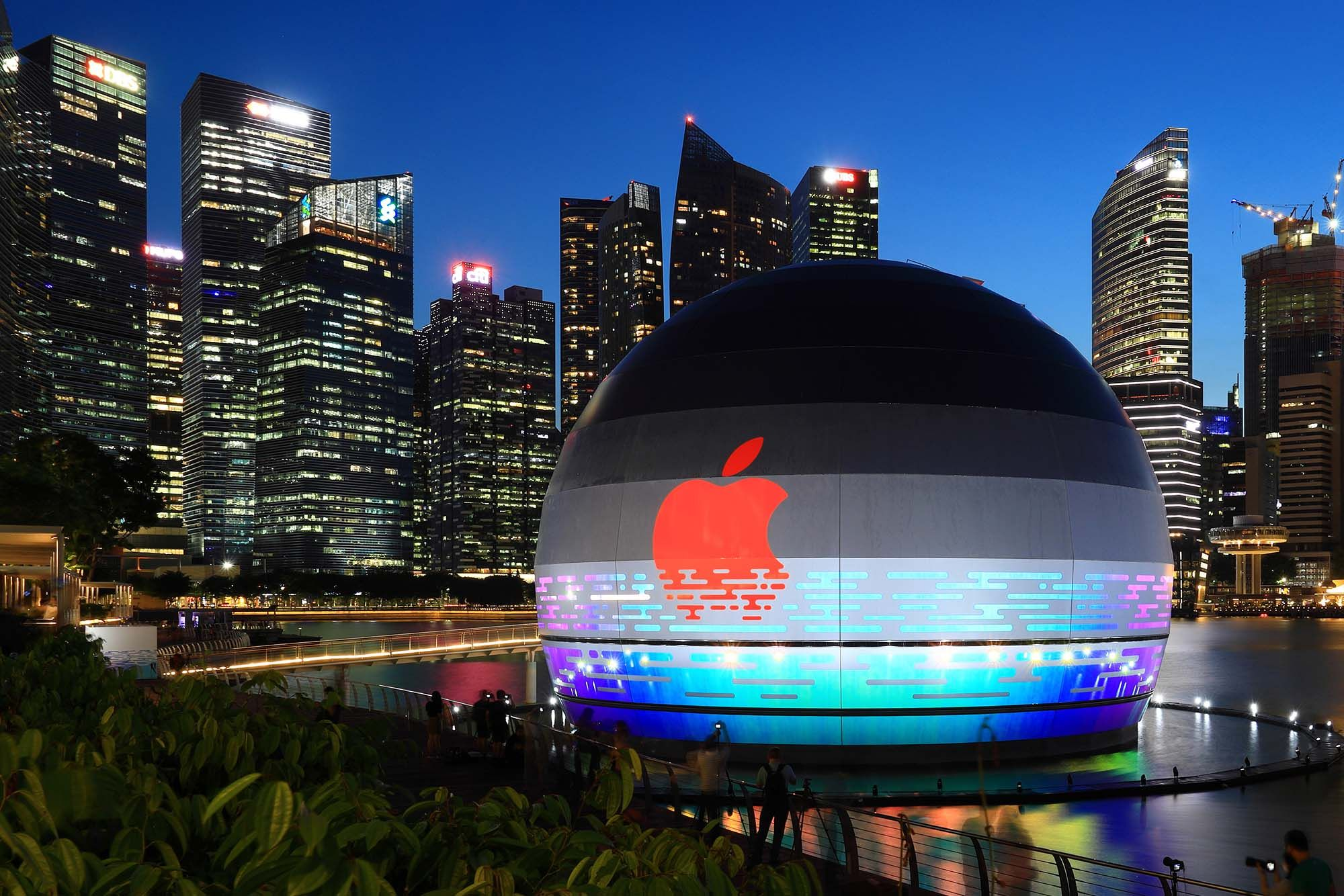 People take photos of the new Apple flagship store against the city skyline at Marina Bay Sands waterfront. (Photo: Getty Images)