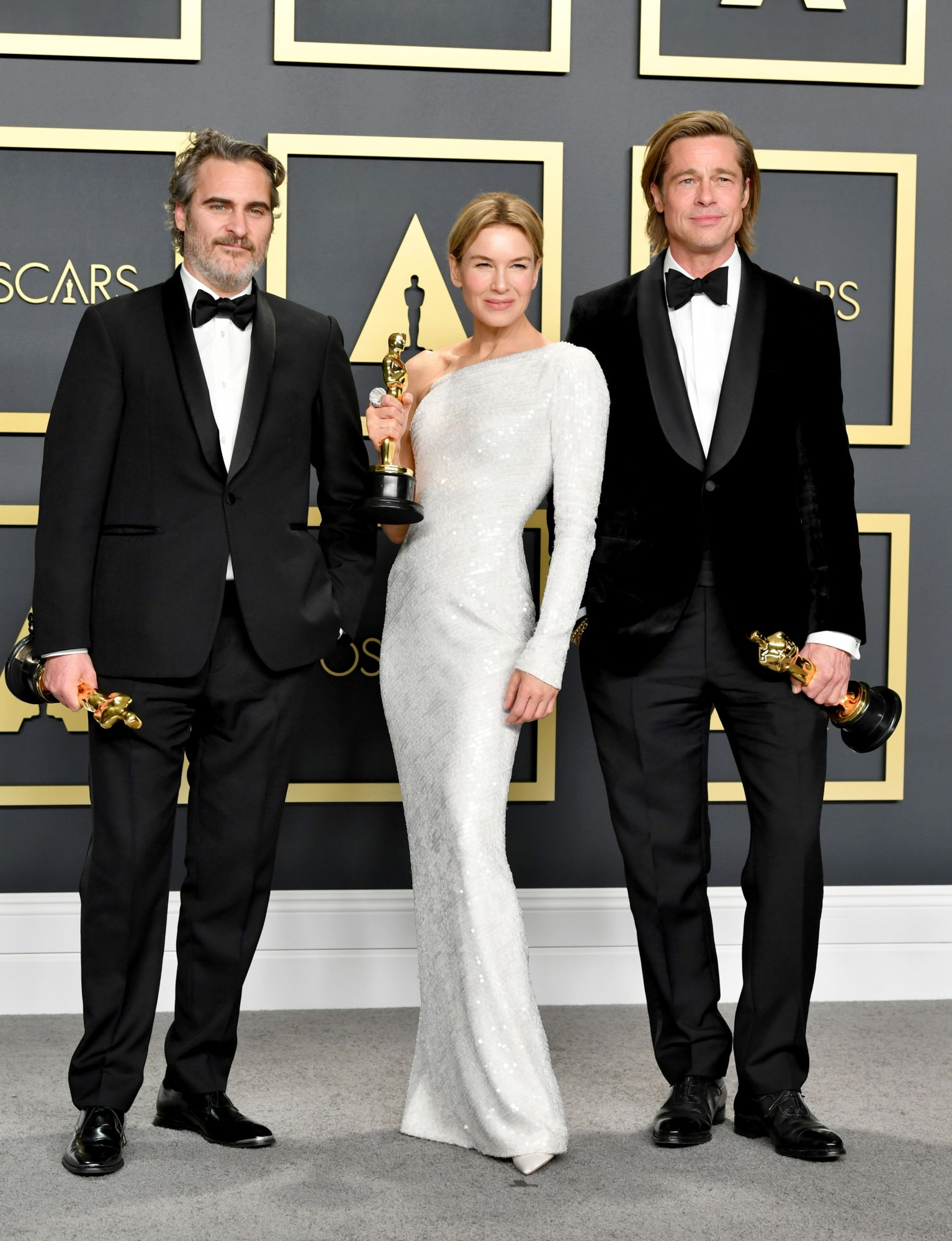 "HOLLYWOOD, CALIFORNIA - FEBRUARY 09: (L-R) Joaquin Phoenix, winner of the Actor in a Leading Role award for ""Joker,"" Renée Zellweger, winner of the Actress in a Leading Role award for ""Judy,"" and Brad Pitt, winner of the Actor in a Supporting Role award for ""Once upon a Time...in Hollywood,"" pose in the press room during the 92nd Annual Academy Awards at Hollywood and Highland on February 09, 2020 in Hollywood, California. (Photo by Amy Sussman/Getty Images)"