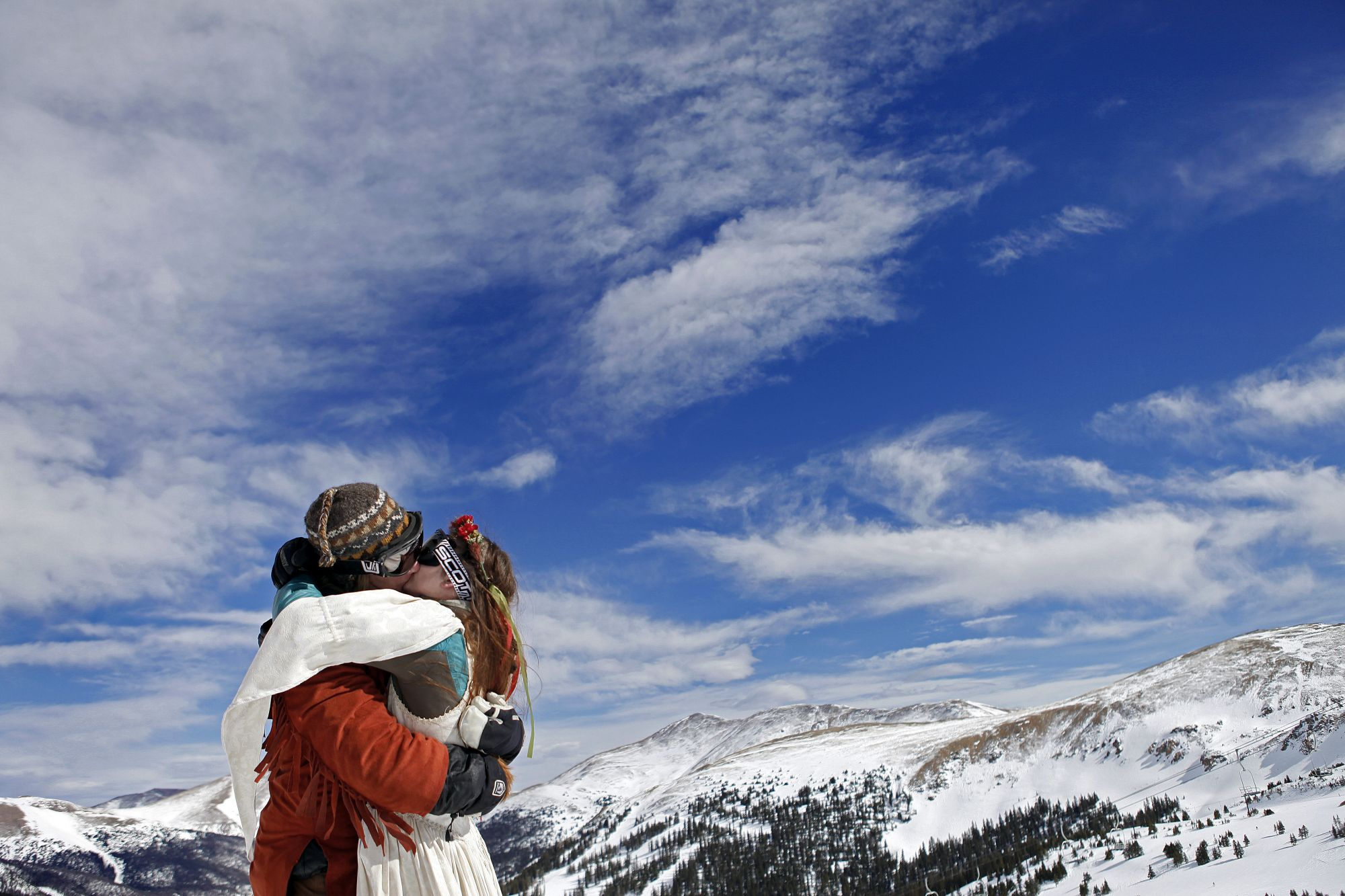 LOVELAND SKI AREA, CO - FEBRUARY 14: Elaine Vardamis (R) of Nederland, Co. kisses her husband Dan Vardamis after the couple renewed their vows at Loveland Ski Area in Colorado at the 20th Annual Marry Me & Ski Free Mountaintop Matrimony on Valentine's Day, February 14th in Loveland, Colorado. The mass wedding ceremony was held at noon at 12,050 feet outside of the Ptarmigan Roost Cabin at Loveland. More than 75 couples were pre-registered to get married or renew their vows high on The Continental Divide in