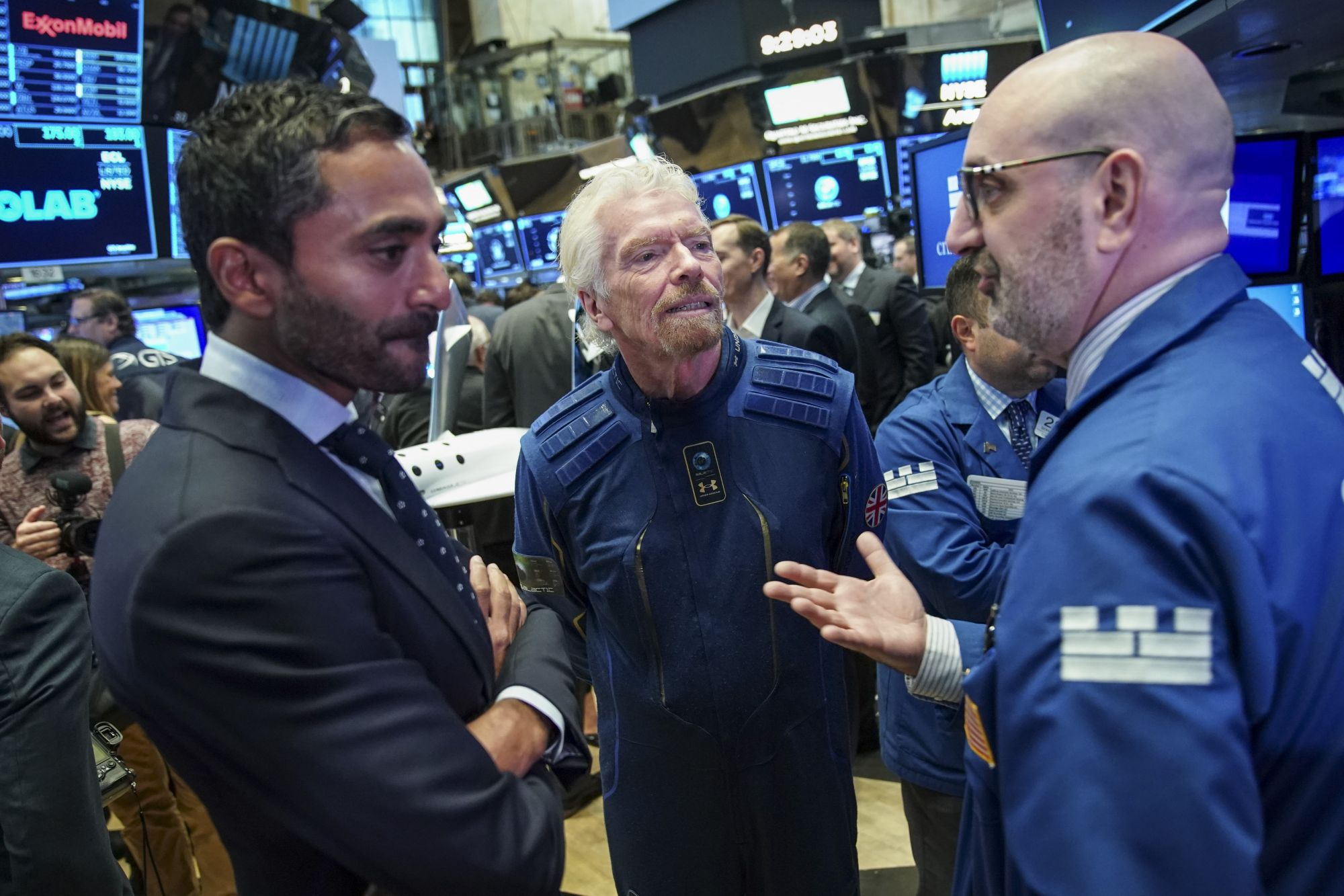 NEW YORK, NY - OCTOBER 28: Sir Richard Branson, Founder of Virgin Galactic, talks with a trader before ringing a ceremonial bell on the floor of the New York Stock Exchange (NYSE) to promote the first day of trading of Virgin Galactic Holdings shares on October 28, 2019 in New York City. Virgin Galactic Holdings became the first space-tourism company to go public as it began trading on Monday with a market value of about $1 billion. (Photo by Drew Angerer/Getty Images)