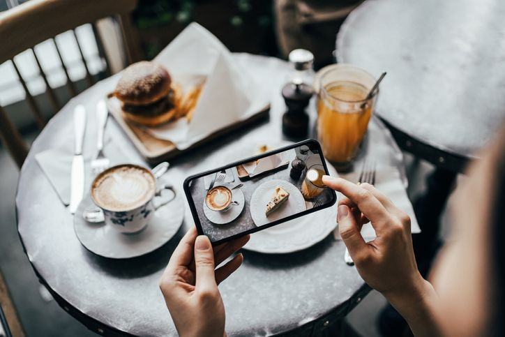 Overhead view of young woman taking photo of freshly served food, burger with fries and cream cake with smartphone and sharing to social media before eating in a stylish coffee shop