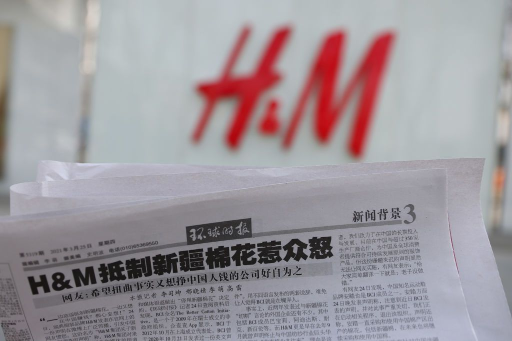 BEIJING, CHINA - MARCH 25: A newspaper with a report about H&M is seen in front of a H&M logo on March 25, 2021 in Beijing, China. (Photo by Jiang Qiming/China News Service via Getty Images)