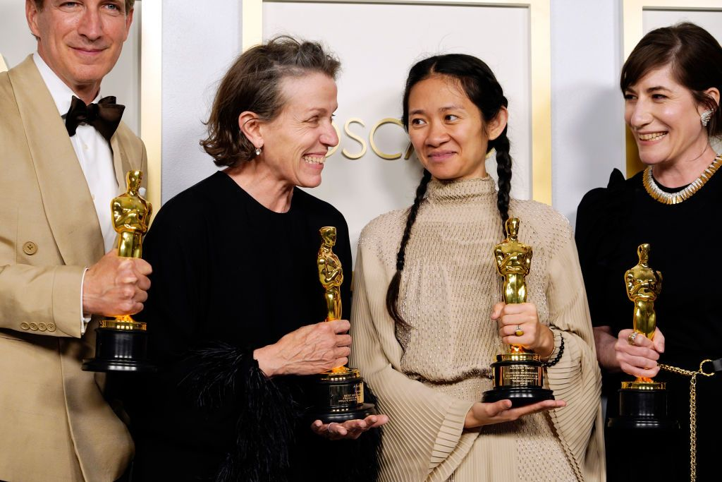 """LOS ANGELES, CALIFORNIA - APRIL 25: (L-R) Peter Spears, Frances McDormand, Chloe Zhao and Mollye Asher, winners of Best Picture for """"Nomadland,"""" pose in the press room at the Oscars on Sunday, April 25, 2021, at Union Station in Los Angeles. (Photo by Chris Pizzello-Pool/Getty Images)"""