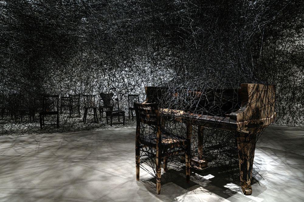 塩田千春,《靜默中》,2002/2021,燒焦鋼琴、燒焦椅、Alcantara黑線,尺寸依空間而定,製作贊助: Alcantara S.p.A.  Courtesy: KENJI TAKI GALLERY, Nagoya/ Tokyo  展出現場:「塩田千春:顫動的靈魂」,臺北市立美術館,2021年。