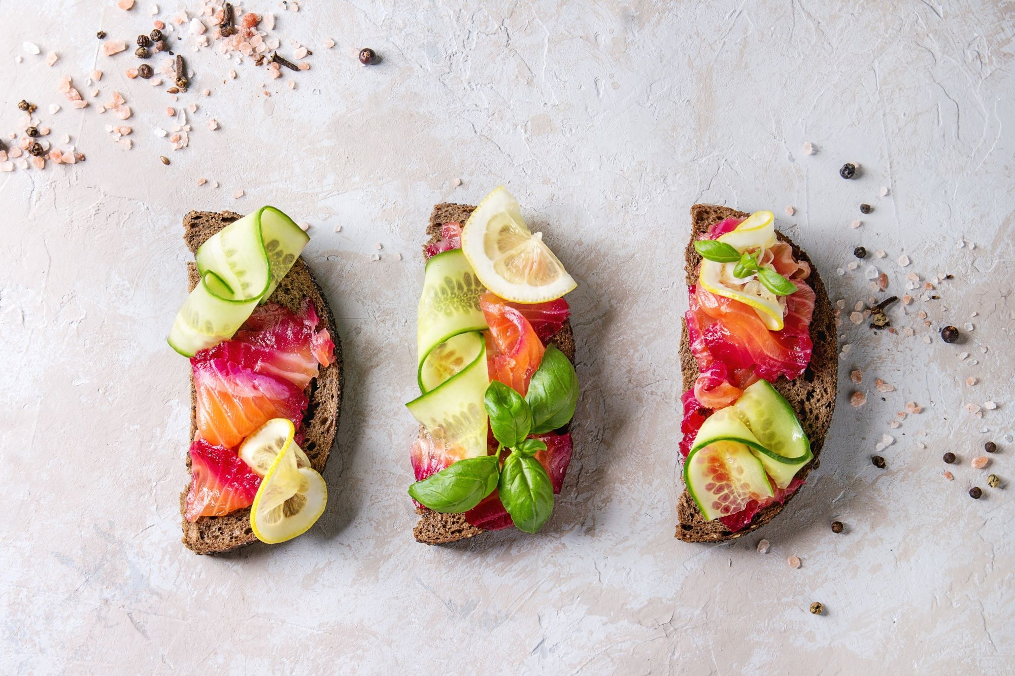 Sliced beetroot marinated salmon sandwiches with rye bread, cucumber, basil and lemon over grey texture background Top view, space. (Photo by: Natasha Breen/REDA&CO/Universal Images Group via Getty Images)