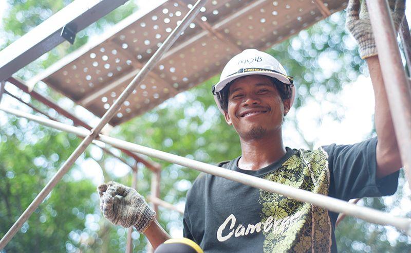 Nasib, a previous home recipient, smiling on the job.