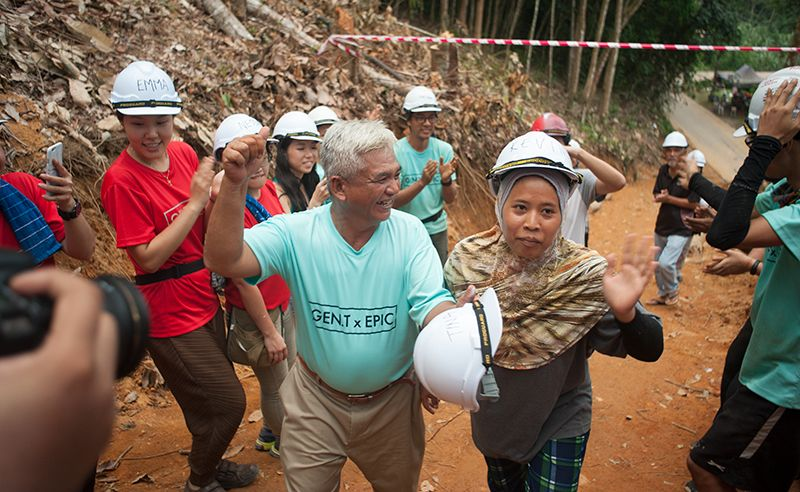 Abang Din and Kak Senum getting the celebrity treatment as they walk towards their newly built home.