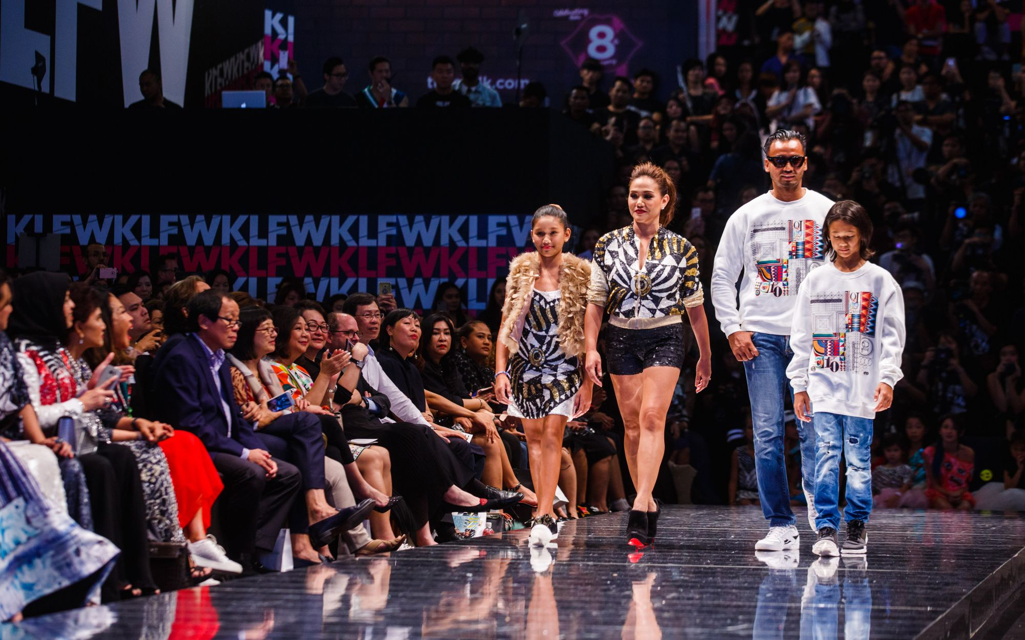 Elyna Effendi and Casmad Sanuri walks down the runway with their children Elyca and Mecael