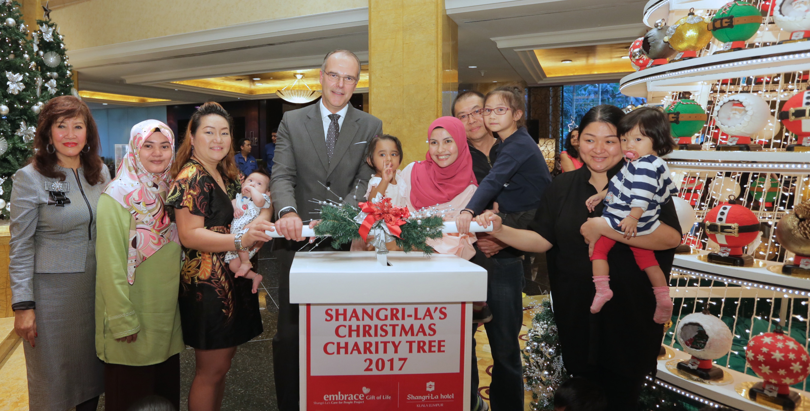 Dato' Rosemarie Wee and the six recipients of the charity fund help Manfred Weber (4th from left) light up the tree