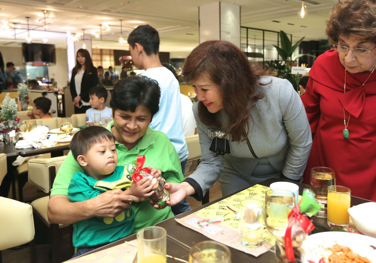 Area director of communications Dato' Rosemarie Wee handing out Christmas cookies to the kids