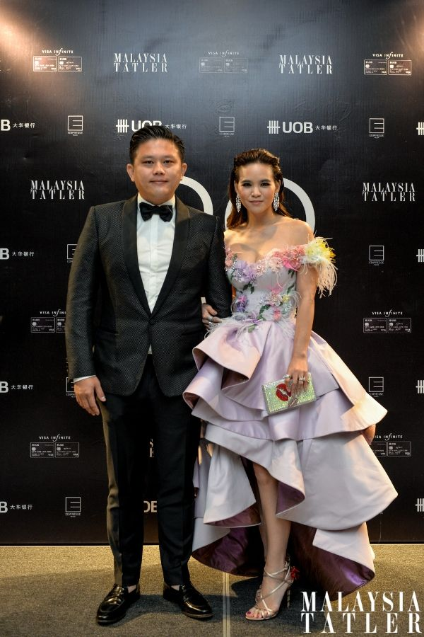 Eu Jin Leow in Dolce & Gabbana and Rolex Submarina watch, and Melissa Sin in Michael Koh