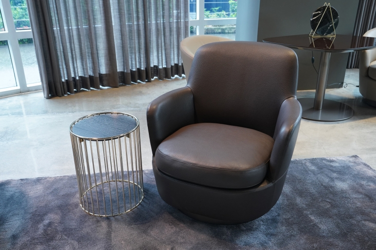 An armchair from the Jacques collection with elegant stitching that emphasizes its curved silhouette.JPG