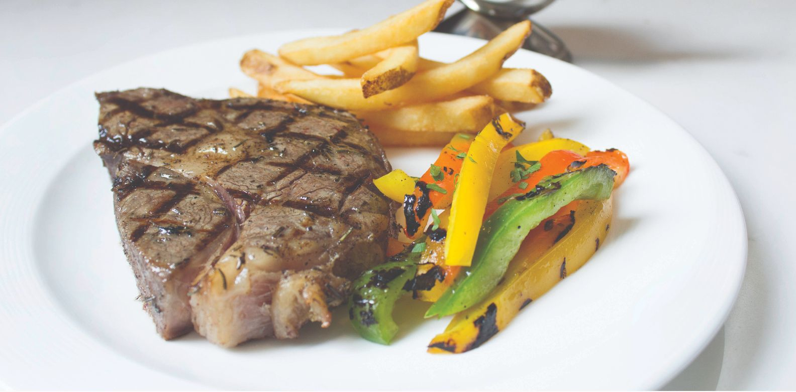 U.S. prime rib-eye with porcini sauce, grilled vegetables, and truffle fries