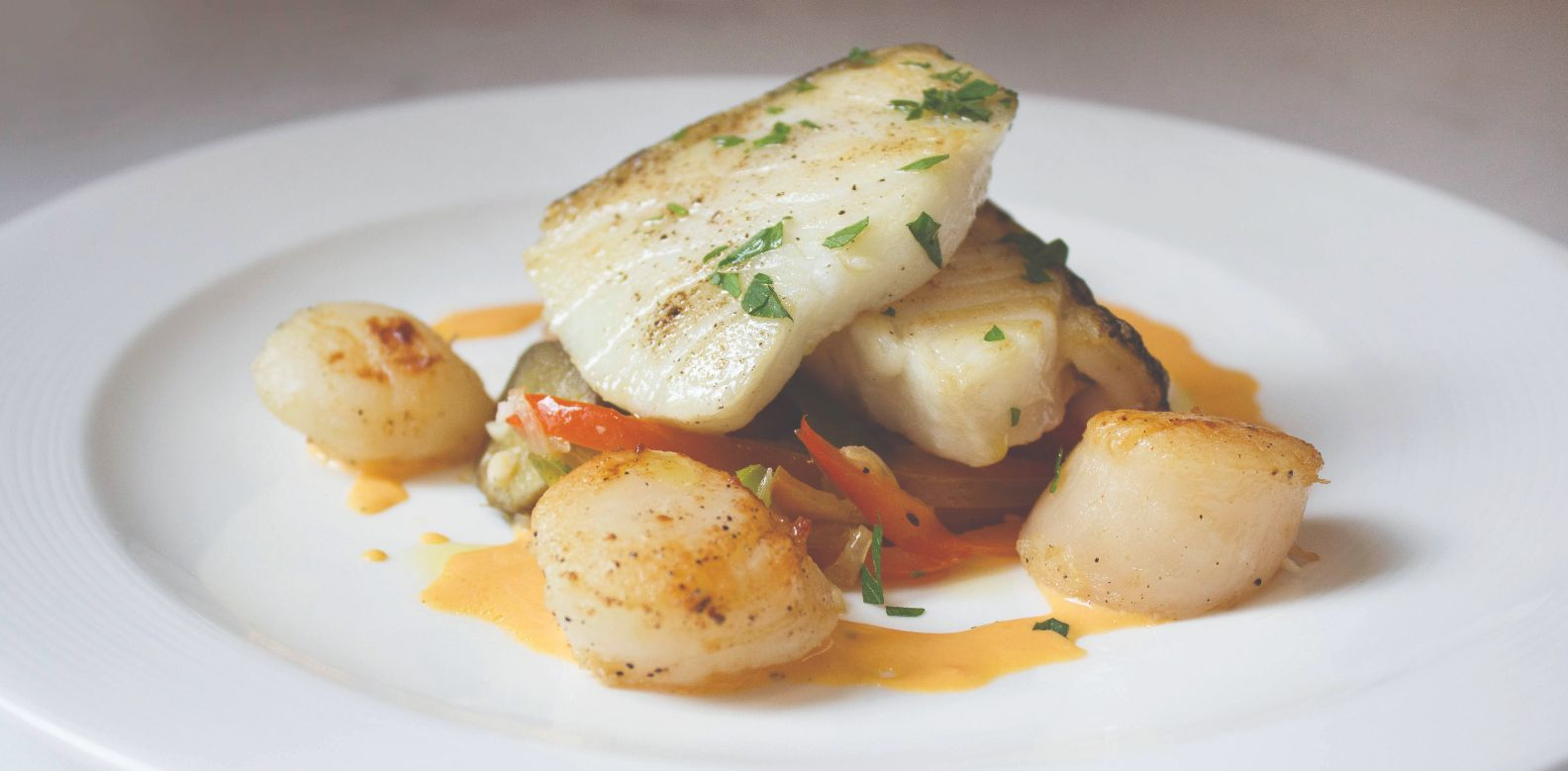 Grilled duo of Chilean sea bass, scallop, and vegetable bayaldi gratin