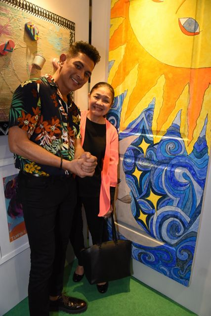 Gary Valenciano and Angeli Pangilinan Valenciano strike a pose beside Kiana Valenciano's door artwork entitled Sun & Moon.