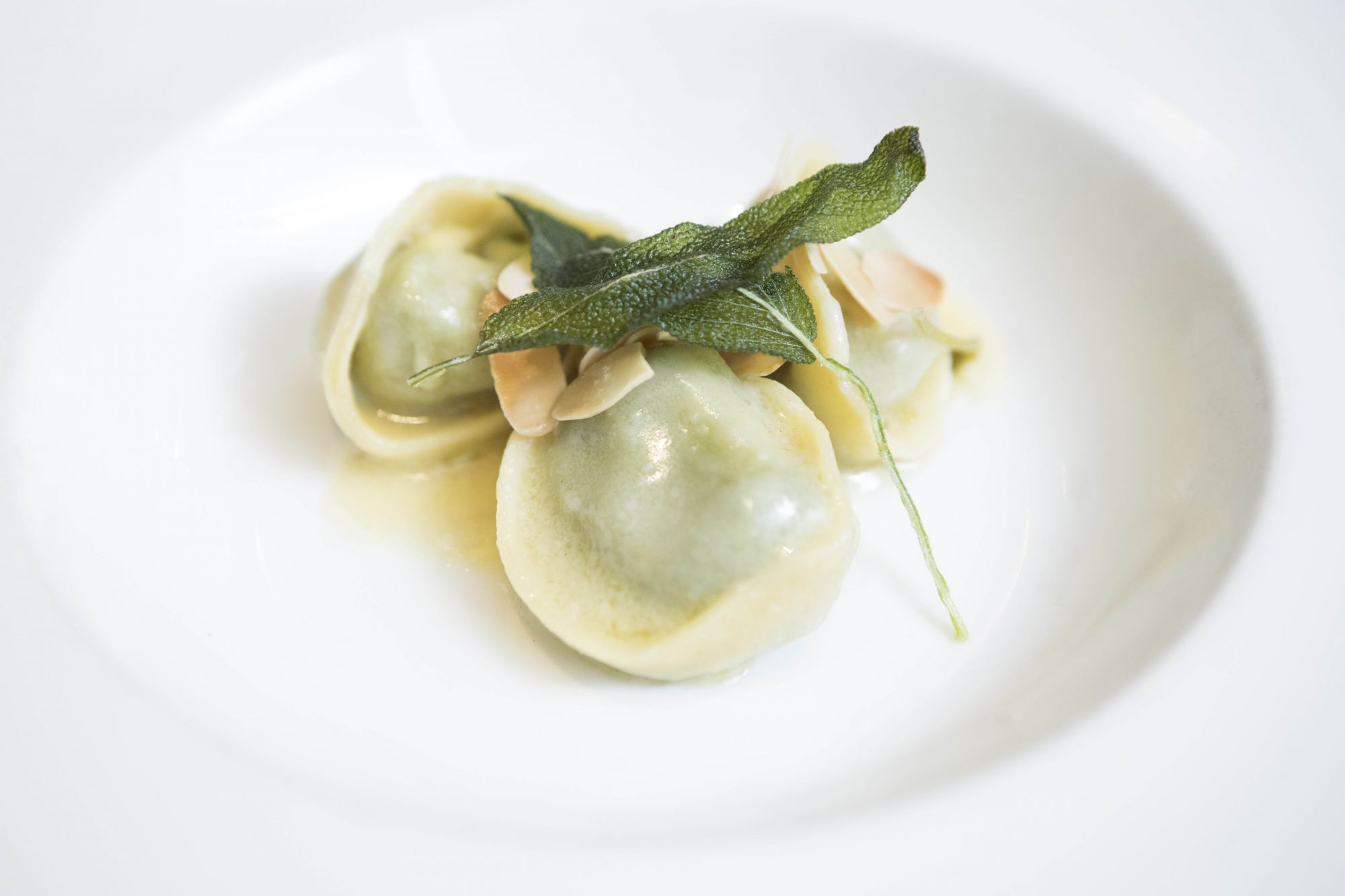Fresh spinach and mushroom tortelli in butter and sage sauce, topped with toasted almonds