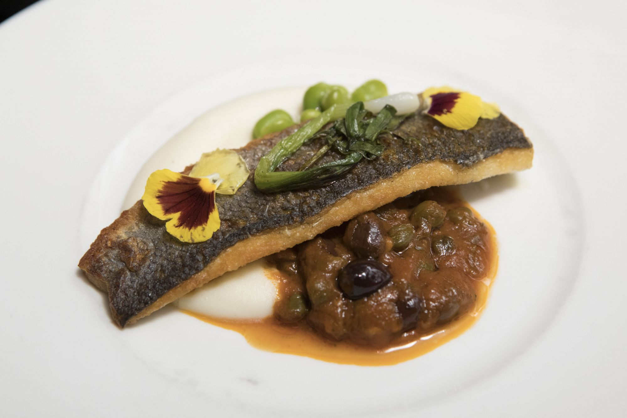 Pan-seared sea bass Mediterranean-style with broad beans and grilled spring onions