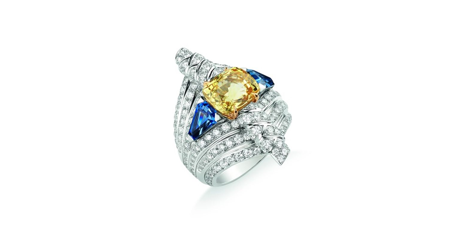 Ring in white gold and yellow gold, set with a 5.61-carat cushion-cut yellow Ceylon sapphire, two troidia-cut sapphires of 1.30 carats each, and brilliant-cut diamonds. Ronde de Pierres, Trésors d'Afrique, Chaumet