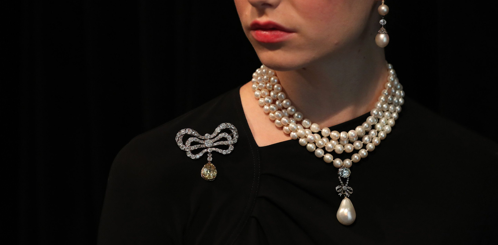 A model wears The 'Queen Marie Antoinette's Pearl' with an estimated value of £767,500-£1,534,000 GBP (872,500-1,743,000 Euros, $1,000,000-2,000,000 USD) on Queen Marie Antoinette's pearl and diamond necklace, together with a Queen Marie Antoinette's diamond brooch (L) during a photocall for the sale of 'Royal Jewels from the Bourbon Parma Family' at Sotheby's auction house in London on October 19, 2018. One of the most important royal jewellery collections ever to come to auction comes for sale at Sotheby'