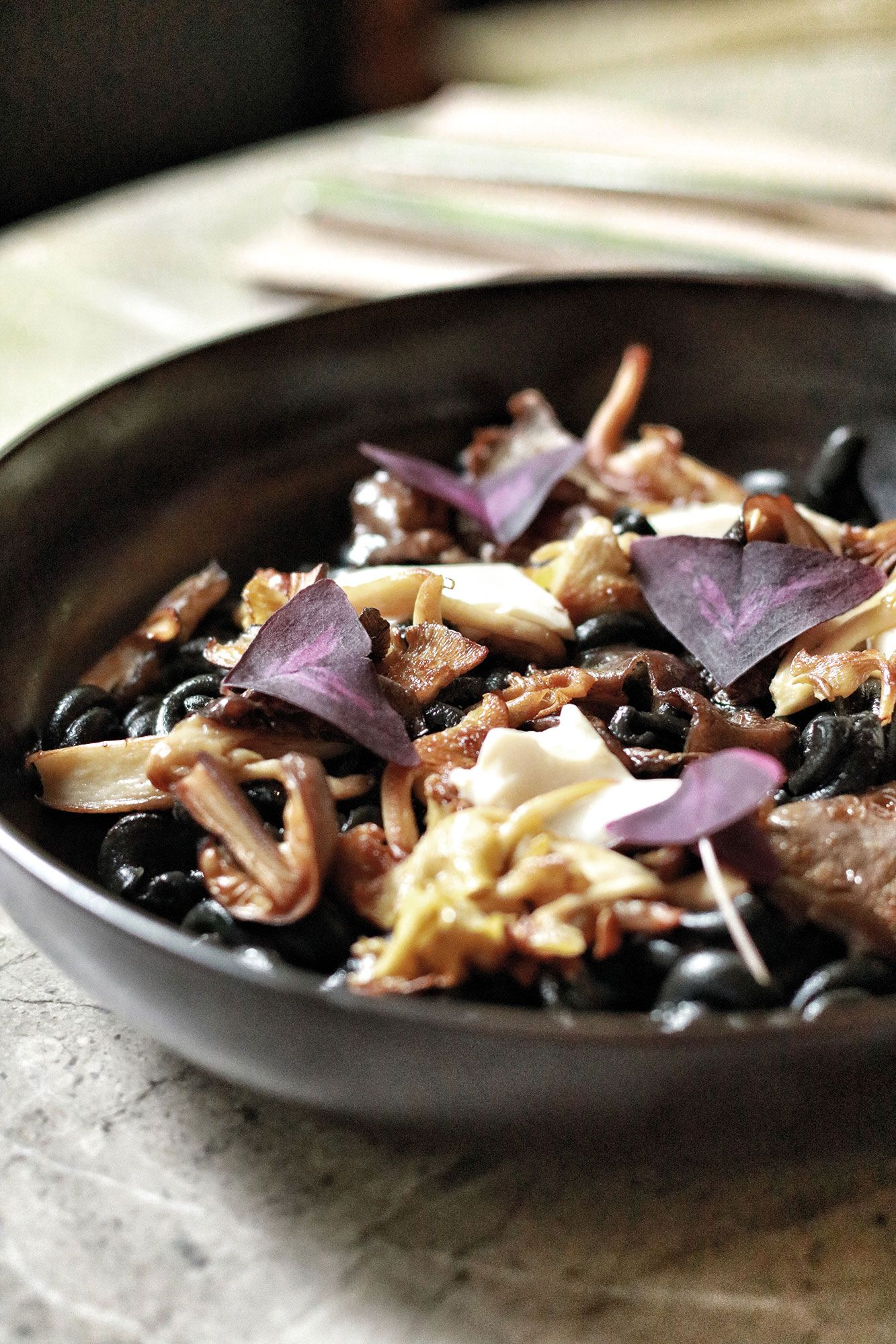 Fermented black beans topped with purple butterfly sorrel (Photo courtesy of Open Farm Community)