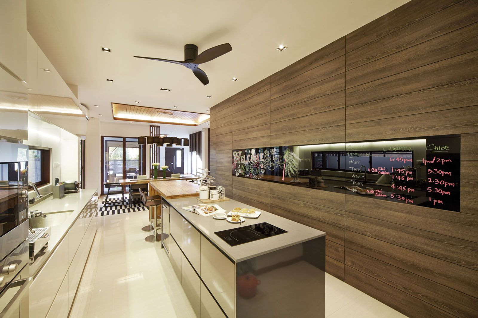 A matte black signature series fan floats above a modern kitchen designed by kgid