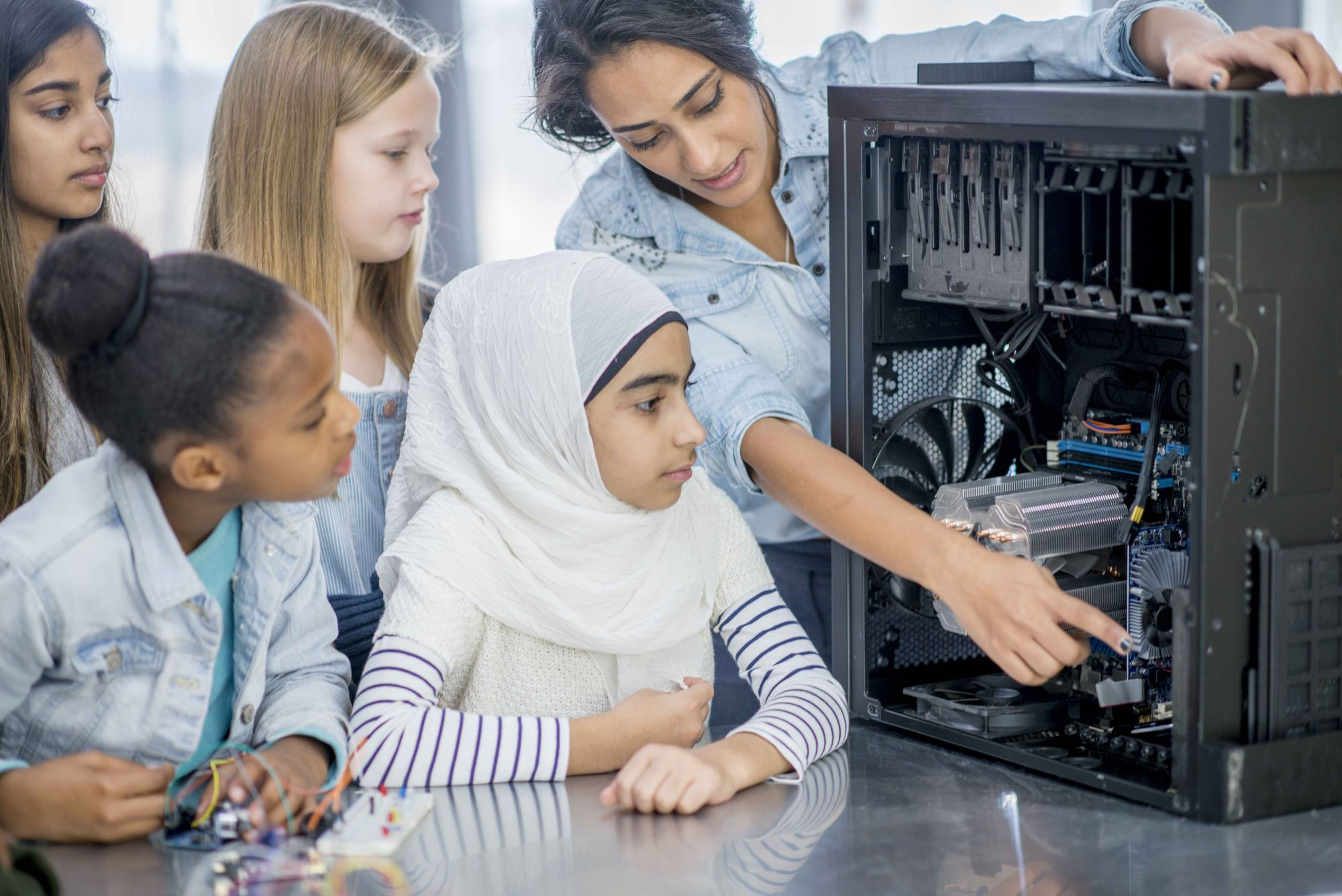 A group of elementary school children and their teacher and indoors in their classroom. The teacher has opened a desktop computer to view the inside components. She is pointing to certain parts and explaining what they do.