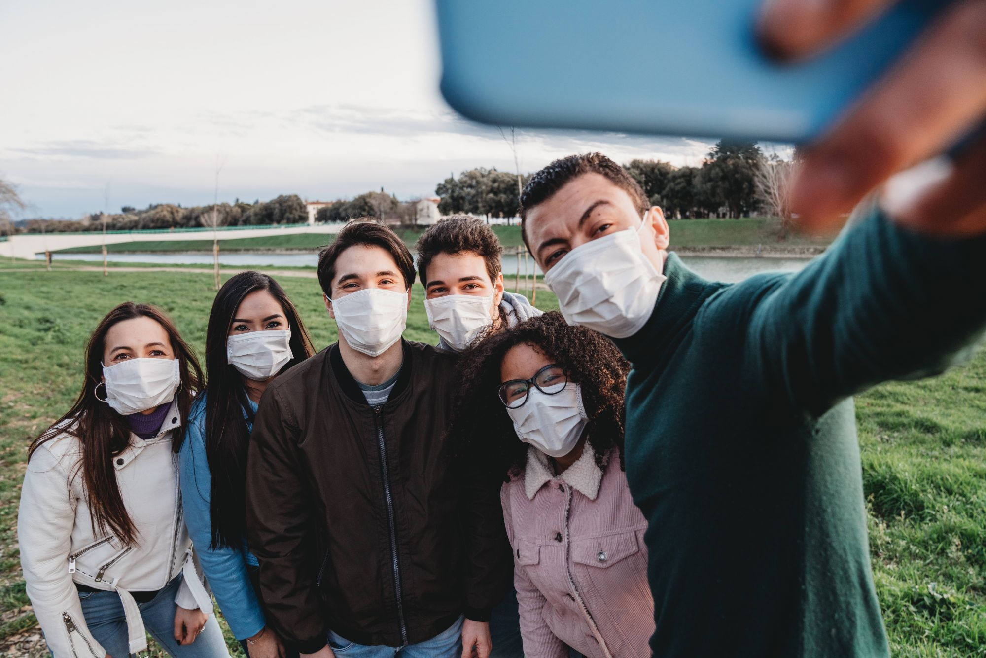 Group of six friends taking a selfie together while they are wearing protecting masks. Multi ethnic group of people wearing pollution masks to protect themselves from viruses.